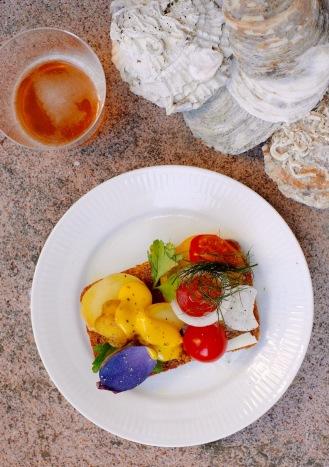 Smørrebrød, czyli otwarte kanapki, przygotowane na domowego wypieku żytnim razowcu. Na jednej połówce kolorowe ziemniaki i sos holenderski, a na drugiej: kolorowe pomidory i cebulka.